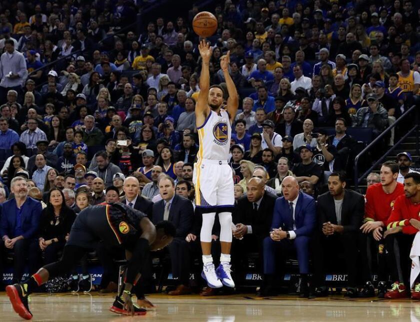 El jugador de los Warriors Stephen Curry (d) lanza a canasta ante Dennis Schroeder (i) de los Hawks durante un partido de la NBA. EFE/Archivo