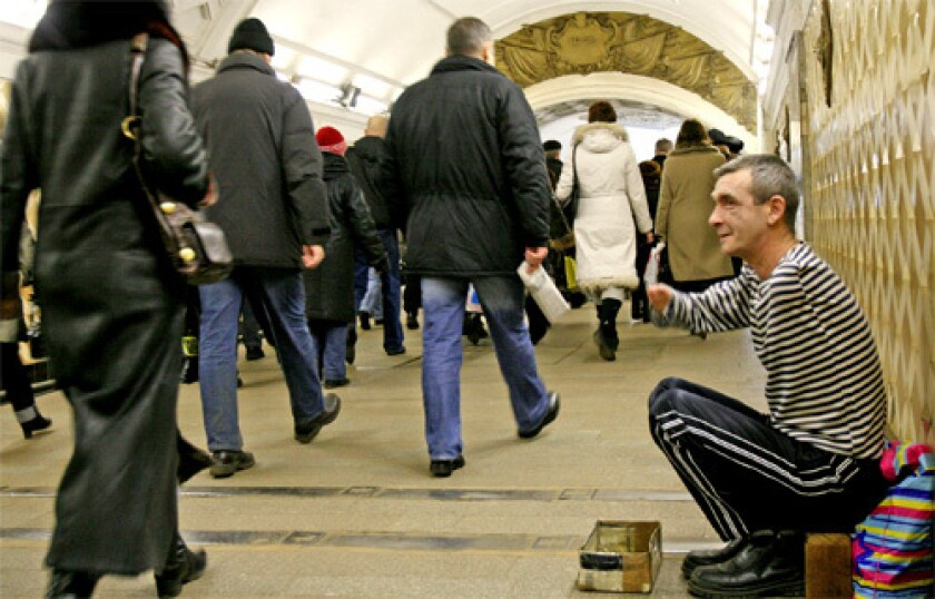 """A disabled man begs in the Moscow Metro. """"When you take that escalator down and look at those faces, get hit with all of that anxiety, all of the worry, it's incredible,"""" one Russian says of the subway."""