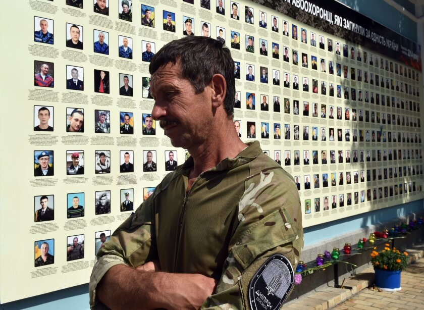 A Ukrainian serviceman reviews a memorial erected in Kiev in late August honoring dead government fighters from the August 2014 battle for Ilovaisk near Donetsk.