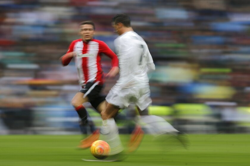 In this slow shutter speed picture Real Madrid's Cristiano Ronaldo, right, runs with the ball during a Spanish La Liga soccer match between Real Madrid and Athletic Bilbao at the Santiago Bernabeu stadium in Madrid, Spain, Saturday, Feb. 13, 2016. (AP Photo/Daniel Ochoa de Olza)