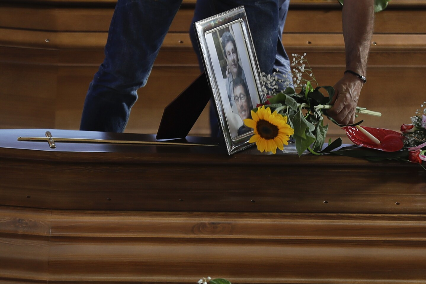 A man lays flowers on a coffin of a victim of Wednesday's earthquake inside a gymnasium in Ascoli Piceno, Italy.