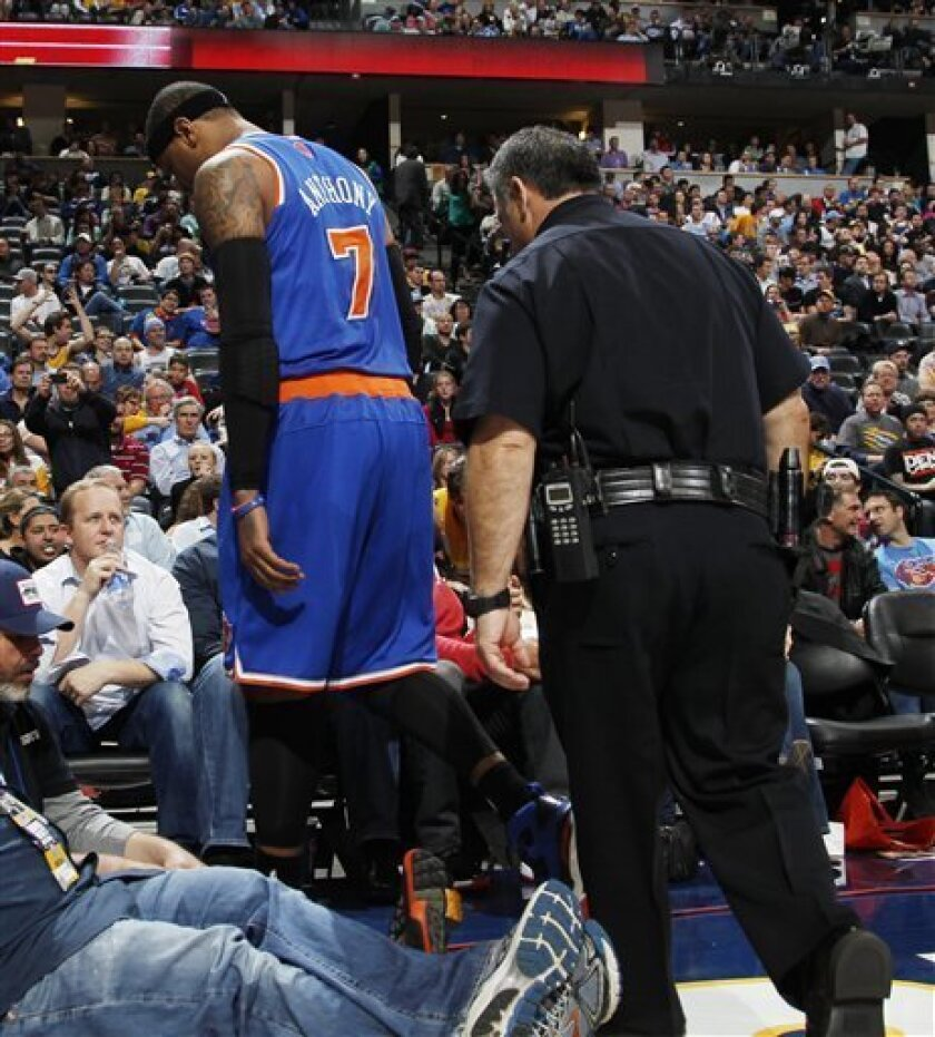 New York Knicks forward Carmelo Anthony walks off the court with a police escort in the third quarter of the Denver Nuggets' 117-94 victory over the Knicks in an NBA basketball game in Denver on Wednesday, March 13, 2013. Anthony left the game, which was his first in Denver since he was traded in 2