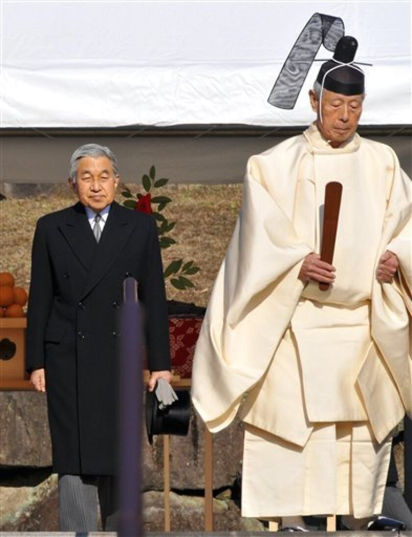 Japan's Emperor Akihito, left, is escorted by a Shinto priest after offering prayers at Musashino Imperial  Mausoleum in Hachioji in the suburbs of Tokyo during the 20th anniversary of late emperor Hirohito's death Wednesday, Jan. 7, 2009. The anniversary comes as the Akihito, 75, has cut back his