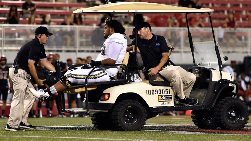 Bruins offensive lineman Tevita Halalilo is driven away after suffering an injury in the final minute of a 37-3 win over UNLV on Saturday night.