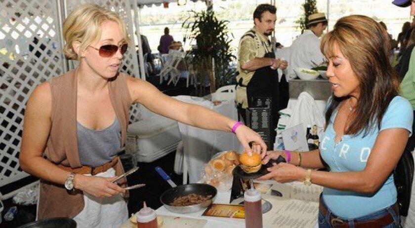 Alex Herman serves Susan Wise a tri-tip slider from Jimmy O's. (Photo: Jon Clark)