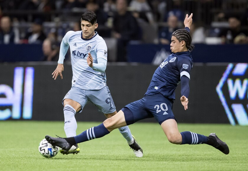 Vancouver Whitecaps' Jasser Khmiri (20) stretches for a tackle against Sporting Kansas City's Alan Pulido (9) during the first half of an MLS soccer game in Vancouver, British Columbia, Saturday, Feb. 29, 2020. (Darryl Dyck/The Canadian Press via AP)