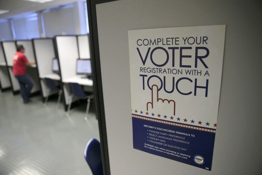 A sign advertises a touch-screen machine, a new process for voter registrat