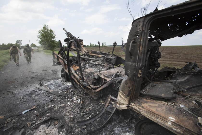 The charred remains of a Ukrainian military armored personnel carrier in the village of Oktyabrskoye, near Kramatorsk, on Wednesday. Six Ukrainian soldiers were killed in an ambush at the site by pro-Russia gunmen on Tuesday.