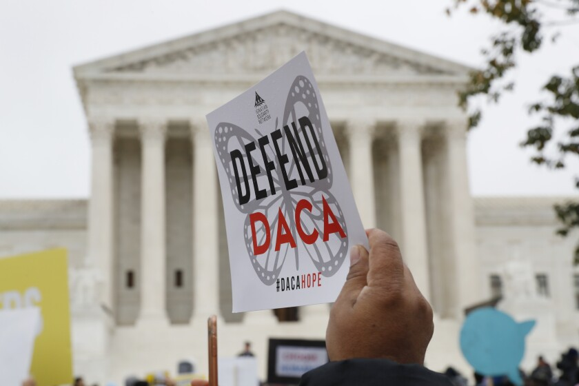 A poster reading 'Defend DACA' is held up outside the U.S. Supreme Court.