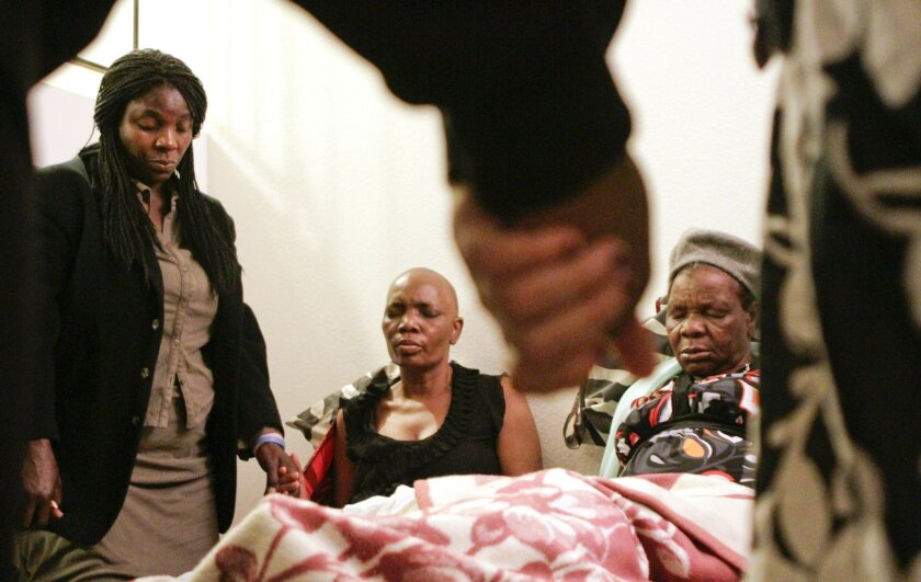 Friends and family members hold hands in a circle as they pray for Tsitsi Mutseta, center left, a local woman from Zimbabwe who is in stage 4 breast cancer, as she sits next to her mother Lucia Mutseta in La Mesa on May 17.