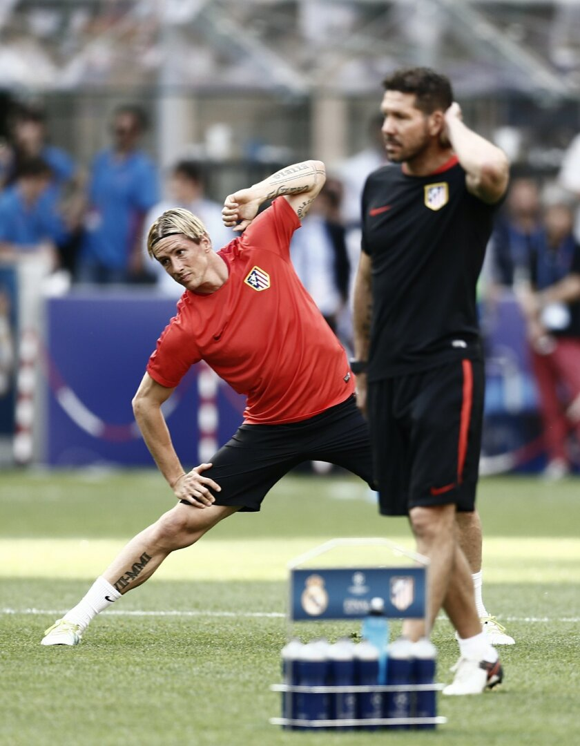 Atletico's Fernando Torres, left, exercises next to coach Diego Simeone during a training session at the San Siro stadium in Milan, Italy, Friday, May 27, 2016. The Champions League final soccer match between Real Madrid and Atletico Madrid will be held at the San Siro stadium on Saturday, May 28.
