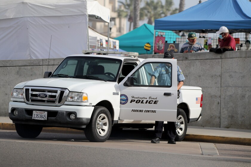 A Huntington Beach Police Parking Control officer exits his truck on Friday.