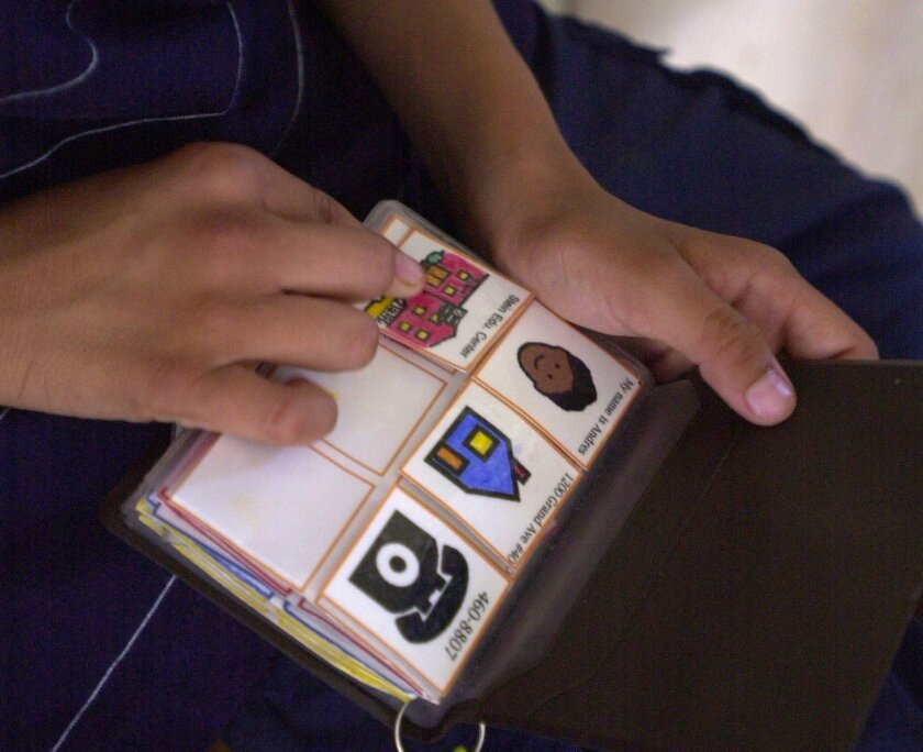 A child with autism uses a picture book filled with small visual cards to communicate with his parents. / photo by Crissy Pascual * U-T San Diego
