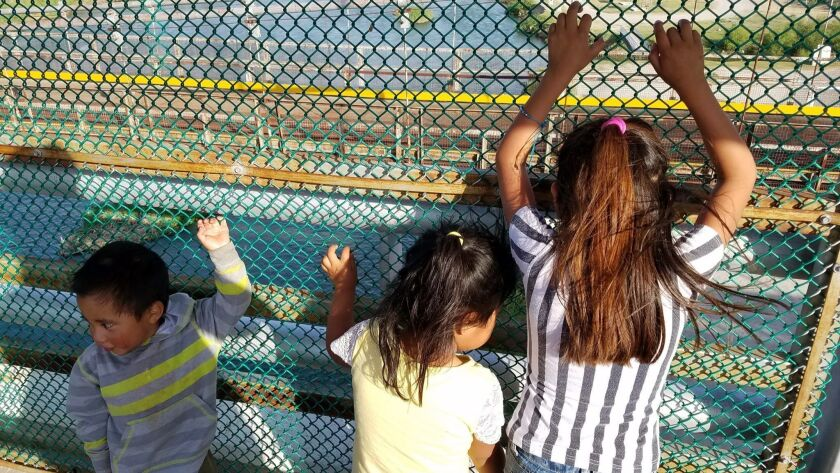 Children from Central America wait on a U.S.-Mexico border bridge to be processed in Texas for asylum consideration.