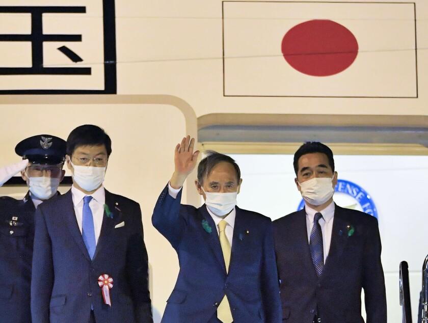 Japanese Prime Minister Yoshihide Suga waves