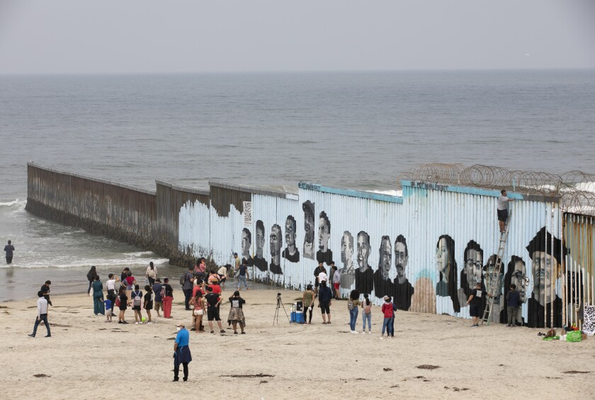 People view a new border mural.