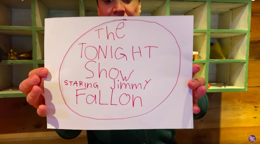 Jimmy Fallon holds a sign for his show made by his daughter.