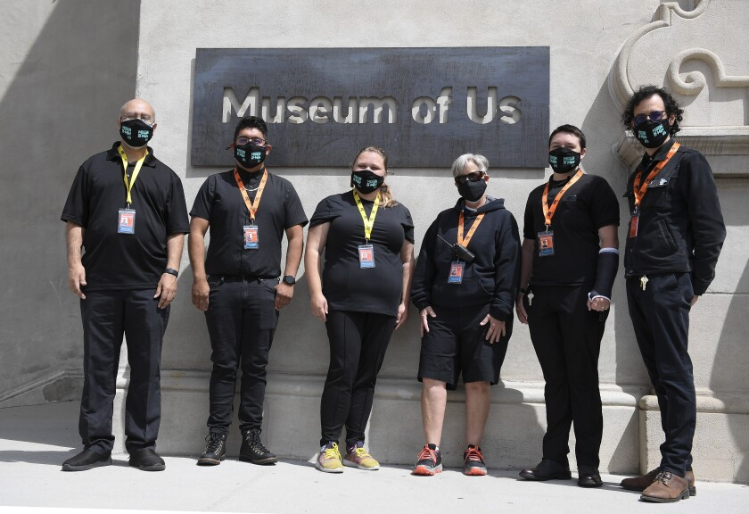 The new visitor experience team outside the new sign for the Museum of Us.