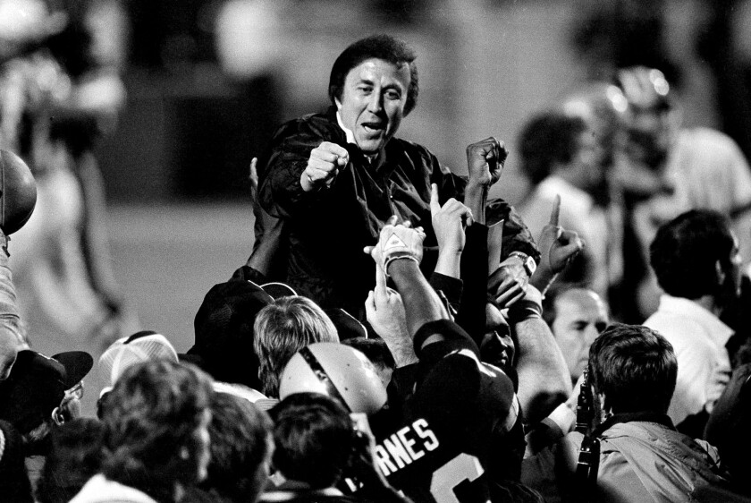 Coach Tom Flores gestures to members of the Los Angeles Raiders as they carry him off the field.