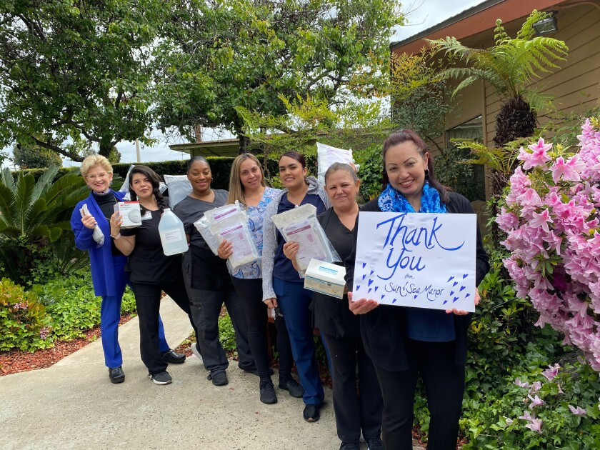 "Dorothy Agustin, Sun and Sea Manor executive director, holds a ""thank you"" sign after the assited living facility received medical supplies from San Diego County. Behind her are the facility's staff and, at left, owner Anne Owens-Stone."