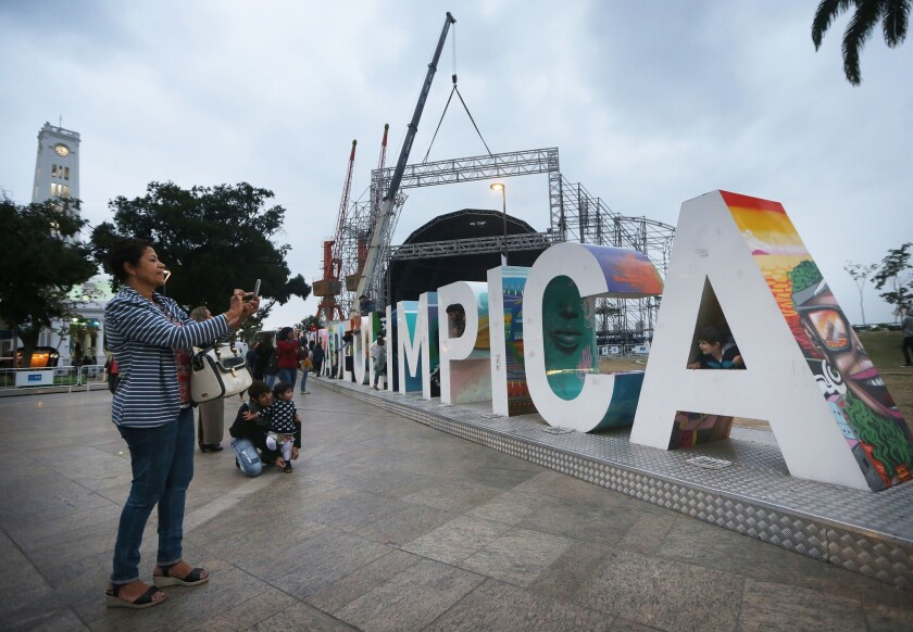 People gather and take photos Wednesday at the Cidade Olimpica sign in the Port District of Rio de Janeiro.