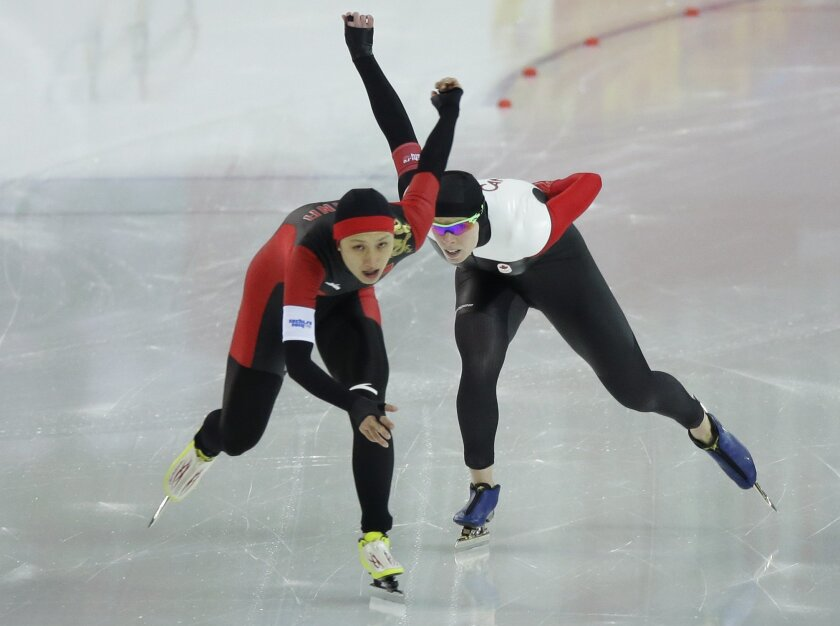 China's Zang Hong, left, and Canada's Christine Nesbitt compete in the women's 1,000-meter speedskating race at the Adler Arena Skating Center during the 2014 Winter Olympics in Sochi, Russia, Thursday, Feb. 13, 2014. (AP Photo/David J. Phillip )