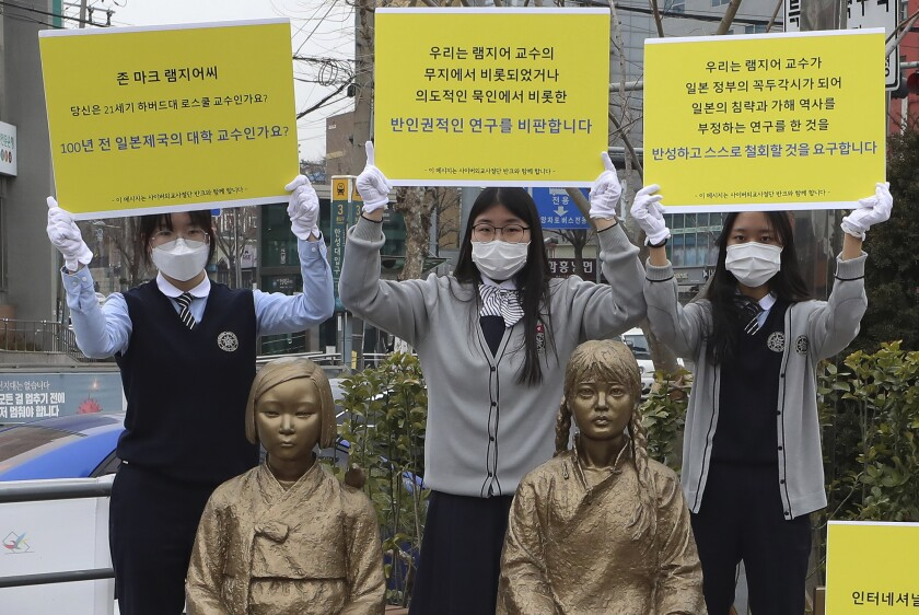 Three Korean girls in masks and school uniforms hold up yellow protest signs next to statues