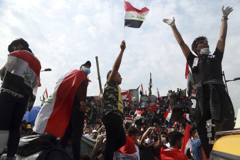 Antigovernment protesters stand Nov. 3  on barriers that Iraqi security forces set up to close a bridge in Baghdad.
