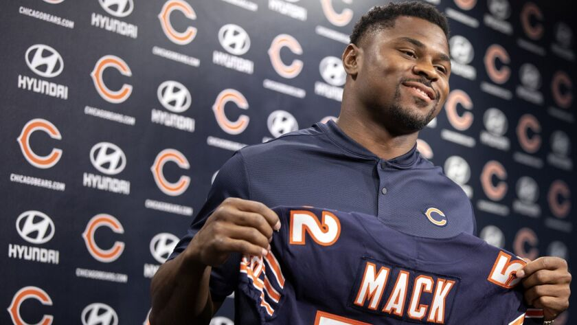 Bears pass rusher Khalil Mack holds up his new jersey during a press conference last Sunday. The Raiders were not willing to pay Mack's asking price.