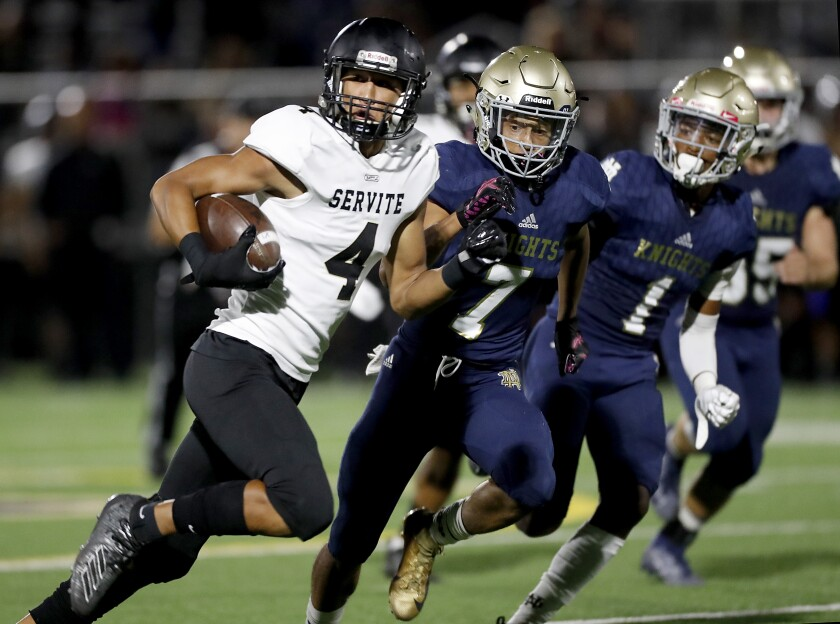 Servite wide receiver Tetairoa Mcmillan gets big yardage after a making a catch against Notre Dame in the second quarter in Sherman Oaks on Friday night.