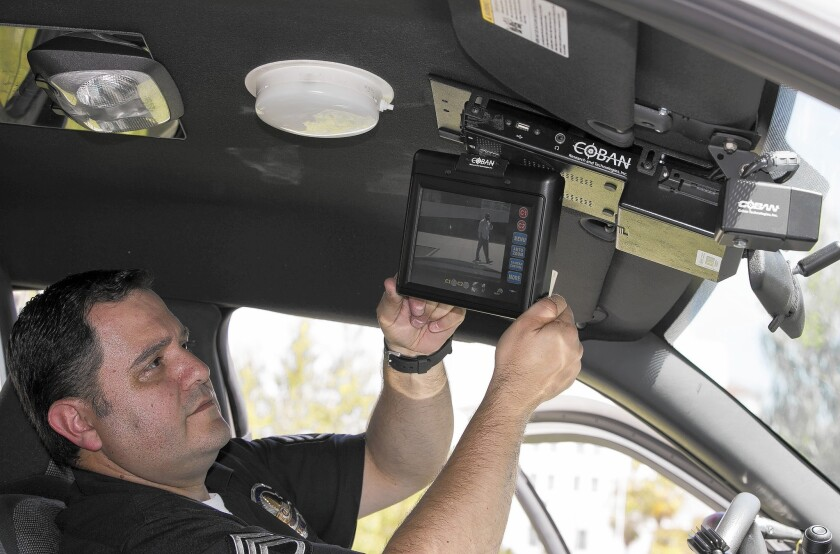 Los Angeles Police Sgt. Dan Gomez, a department expert on recording devices, shows a video display inside a patrol car with a camera pointed through the windshield at right.