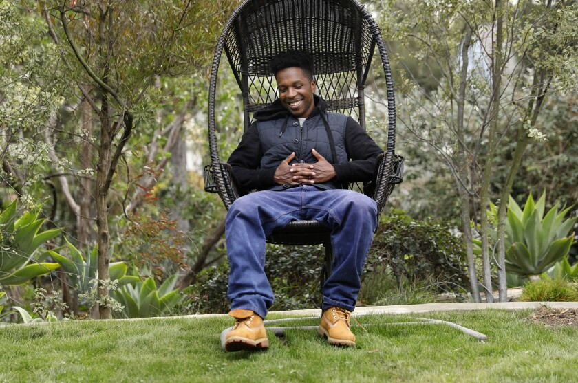 Actor Leslie Odom Jr sits in a hanging chair in his backyard