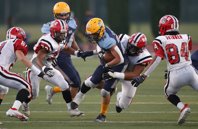 Marina's Dominic Harvey (26) is met by a host of Elsinore tacklers.