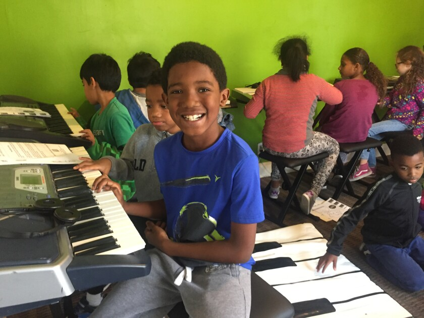 Students learn the piano in one of many classes offered by Los Angeles-based White Hall Arts Academy.