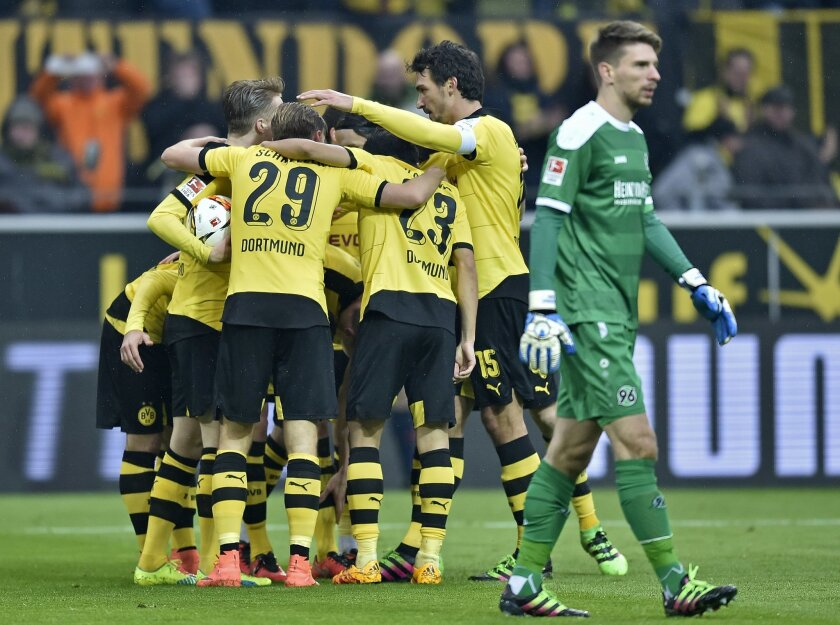 Hannover's goalkeeper Ron-Robert Zieler passes Dortmund's players who celebrate their opening goal during the German Bundesliga soccer match between Borussia Dortmund and Hannover 96  in Dortmund, Germany, Saturday, Feb. 13, 2016. (AP Photo/Martin Meissner)