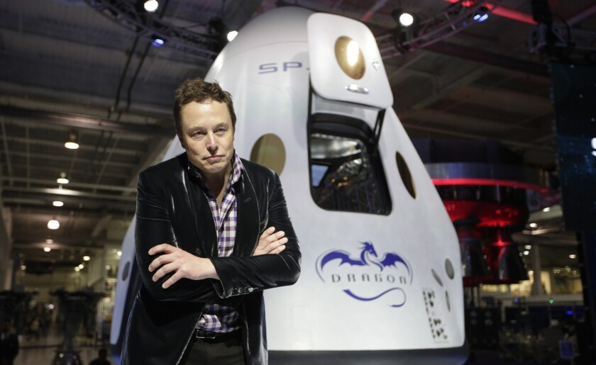 Tesla Motors and SpaceX CEO Elon Musk wants to build cars that can also fly and go underwater. Above, he stands in front of the SpaceX Dragon V2 spaceship at SpaceX's headquarters in May.