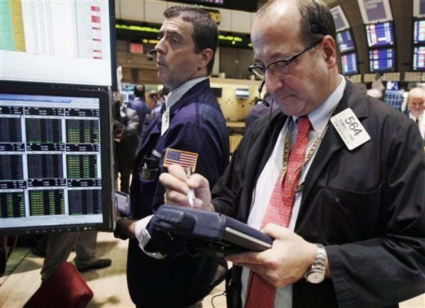In this Tuesday, Oct. 9, 2012 photo, traders Stephen Guilfoyle, left, and Edward Landi work on the floor of the New York Stock Exchange. Stock futures are mixed Wednesday, Oct. 10, 2012, a day after the U.S. earning season kicked off. (AP Photo/Richard Drew)