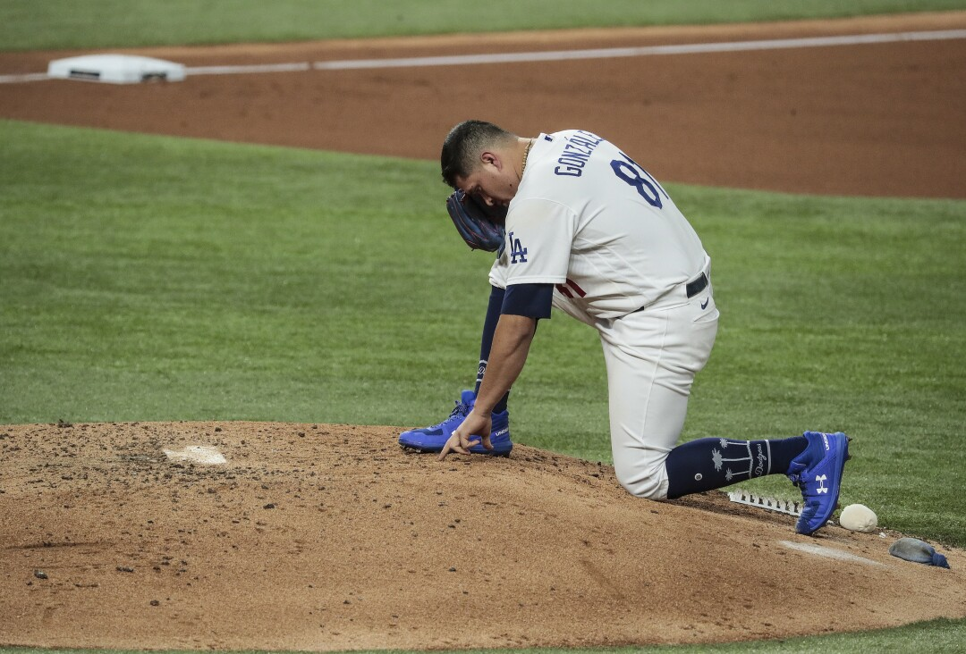 Dodgers reliever Victor Gonzálezwrites in the dirt before pitching in the fifth inning of Game 6 of the World Series.