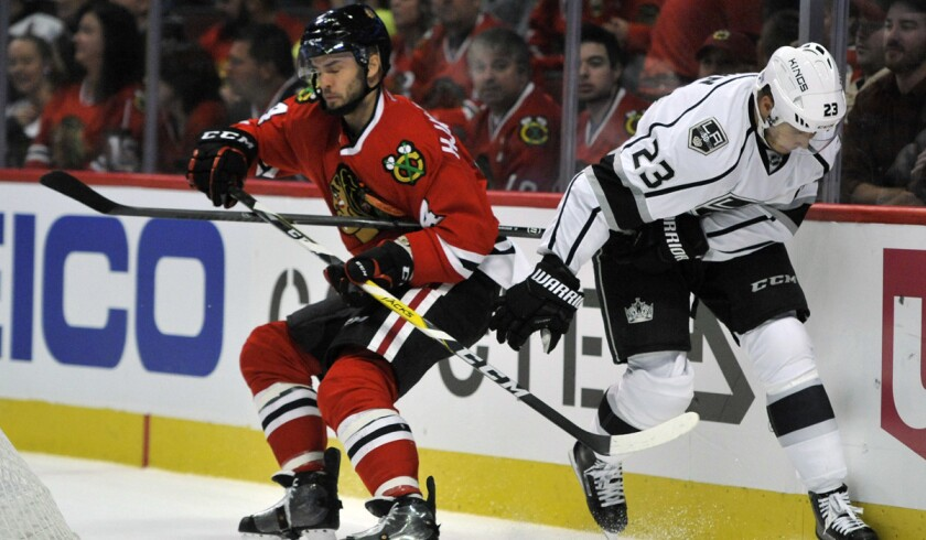 The Kings' Dustin Brown, right, battles Chicago Blackhawks' Niklas Hjalmarsson for the puck during the first period Sunday.