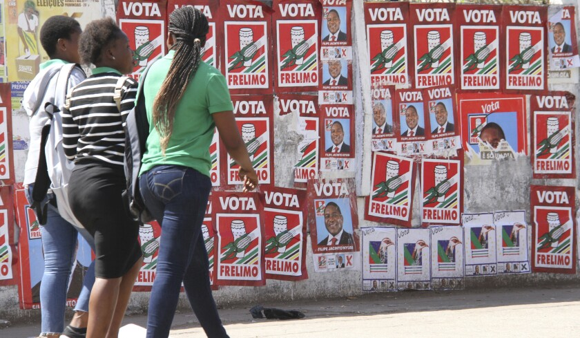 In this photo taken Monday, Sept. 2, 2019 pedestrians pass a wall plastered with election posters in Maputo, Mozambique. The country's elections on Tuesday, Oct 15, 2019 are almost certain to return the ruling party, Frelimo, and President Filipe Nyusi, to power but it is unclear if the results will establish badly needed stability and economic growth. (AP Photo/Ferhat Momade)