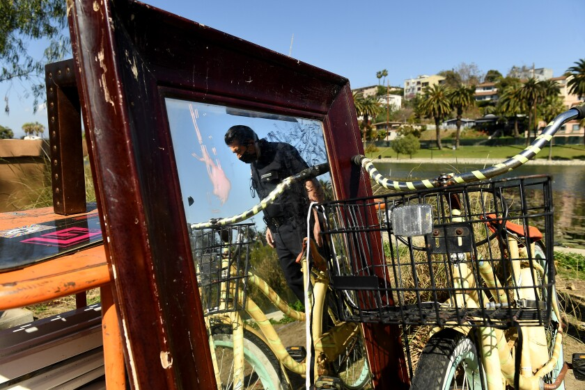 A police officer is reflected in a mirror next to a bicycle in Echo Park.