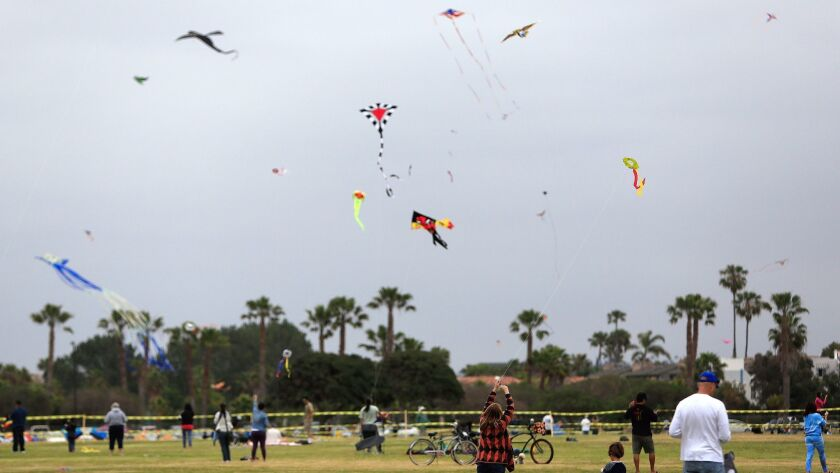 Attendees of the 68th Annual Kite Festival fly their kites high in the sky at Dusty Rhodes Park in Ocean Beach.