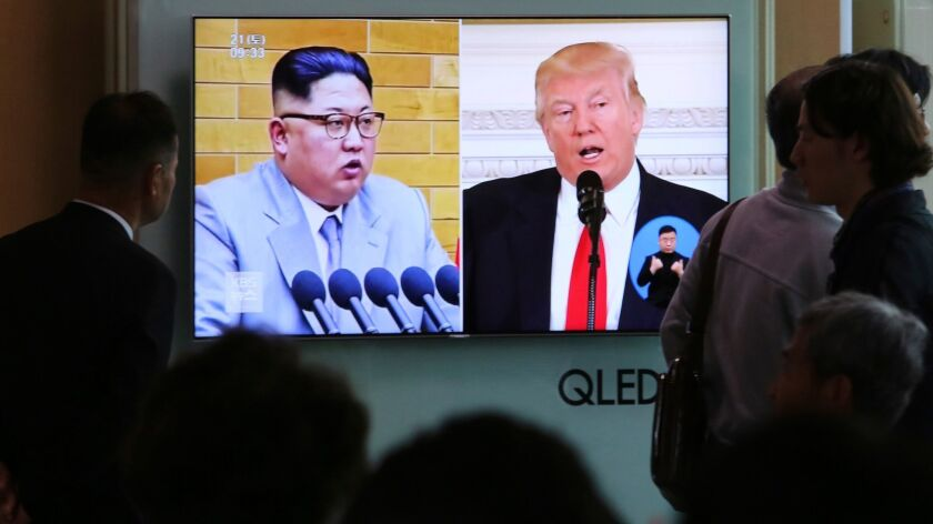 People watch a TV screen showing file footage of North Korean leader Kim Jong Un and President Trump during a news program at the Seoul Railway Station in Seoul.