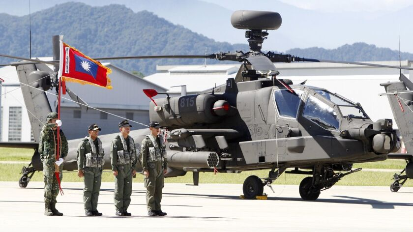 Pilots stand in front of AH-64E Apache attack helicopter before the commissioning ceremony in Taoyua