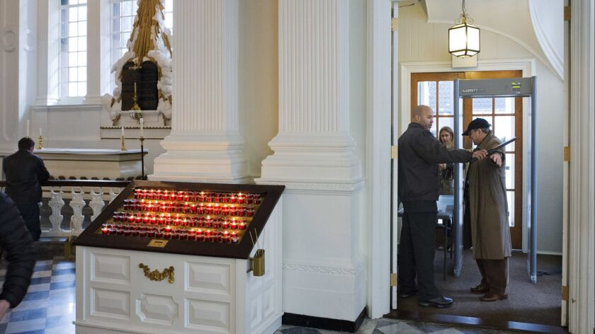 A security guard checks a visitor at the entrance to St. Paul's Chapel in New York.
