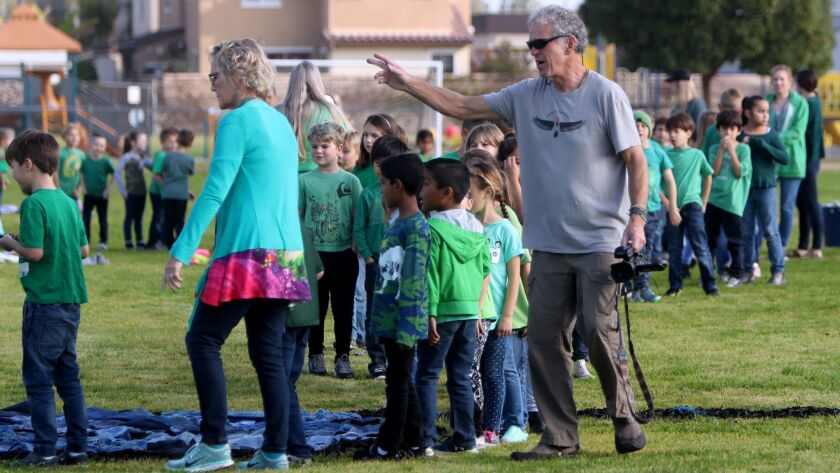 Artist Daniel Dancer, right, directs Woodland Elementary School students to their spots in order to