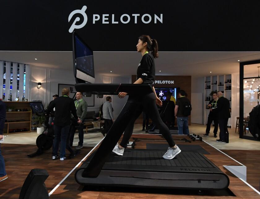 A woman demonstrates using a Peloton treadmill