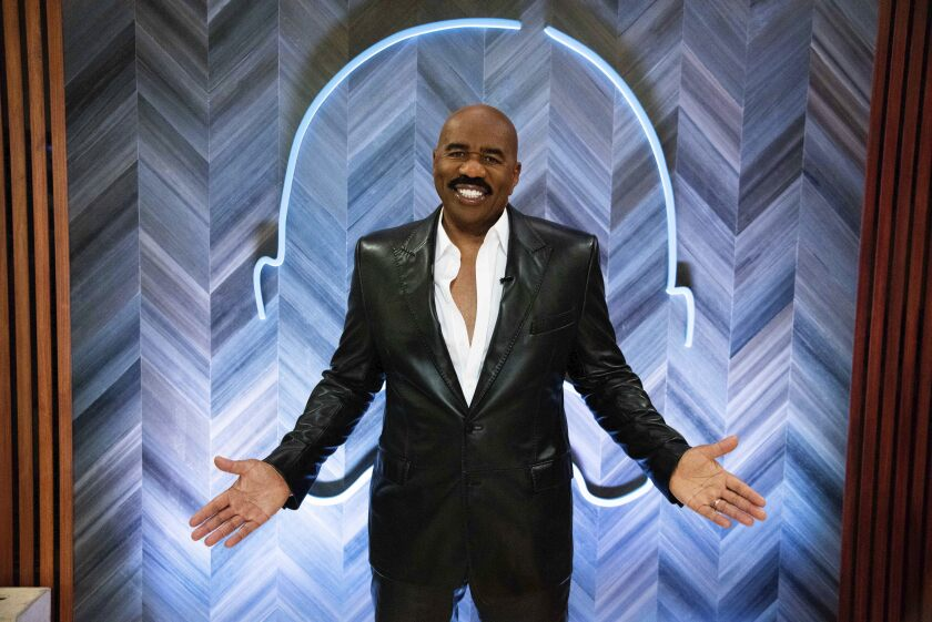 A bald man with a mustache shrugging in a black suit