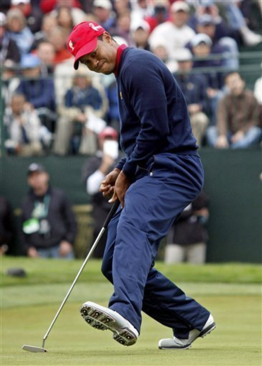 United States Presidents Cup team player Tiger Woods reacts to his birdie putt to win the 9th hole of his singles match at the Presidents Cup at Harding Park Golf Course Sunday, Oct. 11, 2009, in San Francisco. Woods would go on to win the match 6 and 5 and clinch the Presidents Cup for the United States. (AP Photo/Jeff Chiu)