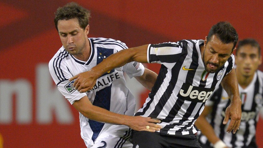 Galaxy defender Todd Dunivant, left, battles Juventus forward Fabio Quagliarella for the ball during an International Champions Cup match on Aug. 3, 2013. Dunivant says MLS players are willing to sit out games if a new collective bargaining agreement is not in place.